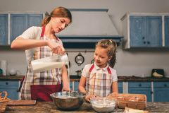Cooking homemade cakes. Happy loving family are preparing bakery together. Mother and child daughter girl are cooking. Cookies and having fun in the kitchen stock images