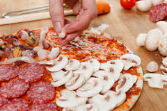 Cooking homemade traditional Italian delicious pizza four seasons Royalty Free Stock Images