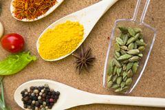 Set of spices and herbs on a corkwood. Cooking hot spicy meal. A set of dry herbs, spices and beans in spoons corkwood background, top view Royalty Free Stock Images