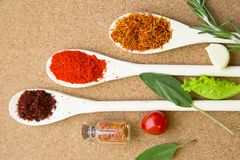 Set of spices and herbs on a corkwood. Cooking hot spicy meal. A set of dry herbs and spices in wooden spoons with fresh tomato and greenery on a corkwood Royalty Free Stock Photo