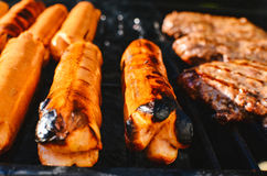 Cooking hotdogs and hamburgers on a grill Royalty Free Stock Photography