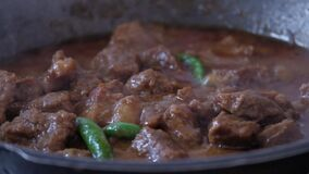 Cooking indian style spicy beef curry, close up
