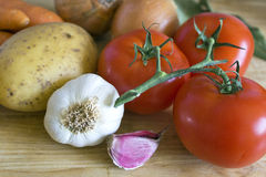 Cooking ingredients. Some carrots, potatoes, onions, tomatoes, garlic and laurel on chopping board Stock Photo