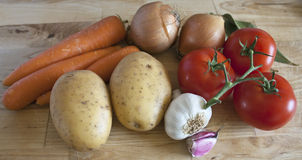 Cooking Ingredients on Chopping Board. Some carrots, potatoes, onions, tomatoes, garlic and laurel on chopping board Stock Images