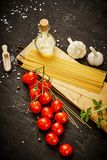 Tomatoes garlic salt olive peppers and pasta on a black table royalty free stock image