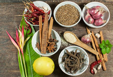 Cooking ingredients. Contains : lemon,Dried chilies,pepper, scallions, cinnamon,star anise, Heliconia thai flower,Garlic and Basil on wooden table Royalty Free Stock Photos