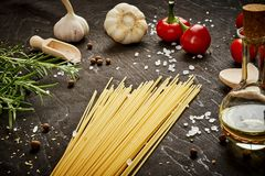 Tomatoes garlic salt olive peppers and pasta on a black table. Cooking ingredients for cooking composed of tomatoes, garlic, salt, olive peppers and pasta on a Royalty Free Stock Photo