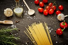 Tomatoes garlic salt olive peppers and pasta on a black table royalty free stock images