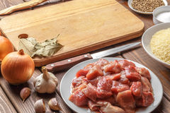 Cooking ingredients. Cutting board. Sliced raw meat, rice, oil, spices, garlic Royalty Free Stock Images