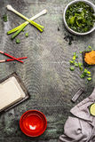 Cooking ingredients for Japanese miso soup: wakame seaweed, Silken tofu, spring onions and Miso paste on aged background, top view Royalty Free Stock Photo