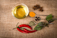 Cooking ingredients, spices, herds and oil on a burlap Royalty Free Stock Photos