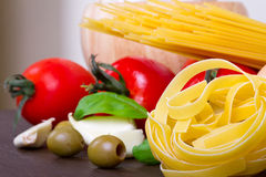 Cooking Italian pasta. Italian food ingredients for cooking with pasta, tomatoes, onion, garlic, basil and olives Royalty Free Stock Images