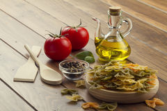 Cooking Italian pasta. Some ingredients in a wooden table for cooking Italian pasta: tomatoes, farfalle, olive oil, peppermint and pepper Stock Photo