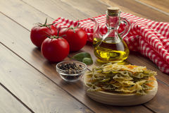 Cooking Italian pasta. Some ingredients in a wooden table for cooking Italian pasta: tomatoes, farfalle, olive oil, peppermint and pepper. A checkered red napkin Stock Photo