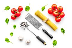 Cooking italian pasta. Spaghetti, tomatoes, garlic, basil and cookware on white background top view.  Royalty Free Stock Photography