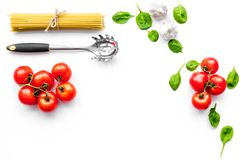 Cooking italian pasta. Spaghetti, tomatoes, garlic, basil and cookware on white background top view copy space. Cooking italian pasta. Spaghetti, tomatoes Royalty Free Stock Photography