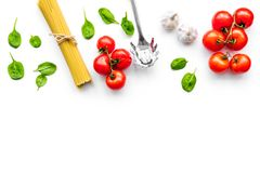 Cooking italian pasta. Spaghetti, tomatoes, garlic, basil and cookware on white background top view copy space. Cooking italian pasta. Spaghetti, tomatoes Stock Photos