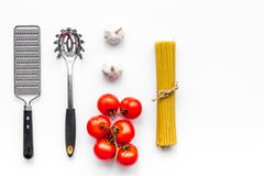 Cooking italian pasta. Spaghetti, tomatoes, garlic and cookware on white background top view.  Royalty Free Stock Images