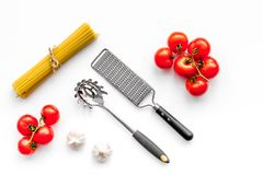 Cooking italian pasta. Spaghetti, tomatoes, garlic and cookware on white background top view.  Royalty Free Stock Photography