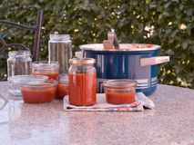 Cooking italian style homemade tomato sauce and preservating in the preservating jars in the garden. Royalty Free Stock Photography