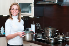 Cooking on kitchen. Beautiful happy smiling woman in kitchen interior standing with pan near kitchen-range. One person only Stock Photo
