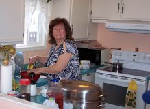 Cooking in the kitchen. Young grand mom preparing the turkey dinner stock photography