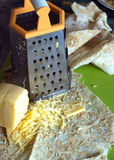 Cooking on kitchen desk. Grater, pita bread and sliced cheese Stock Image