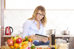 Cooking in the kitchen. Shot of a middle aged woman reading recipe on her digital tablet while preparing healthy food in the kitchen Royalty Free Stock Images