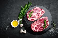 Cooking on kitchen table fresh raw pork marbled steaks on black background. Top view Royalty Free Stock Photo
