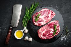 Cooking on kitchen table fresh raw pork marbled steaks on black background. Top view Royalty Free Stock Photos
