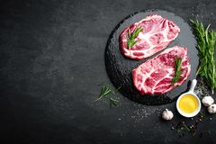 Cooking on kitchen table fresh raw pork marbled steaks on black background. Top view Stock Photos
