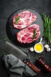 Cooking on kitchen table fresh raw pork marbled steaks on black background. Top view Royalty Free Stock Photography
