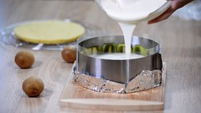 Cooking kiwi mousse cake. Pouring vanilla mousse. Cooking kiwi mousse cake. Pouring vanilla mousse stock footage