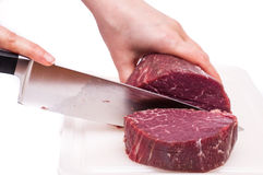 Cooking knife is slicing a fillet of beef Stock Image