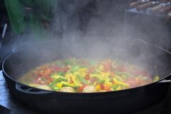 Cooking vegetables in large cast iron cauldron Royalty Free Stock Photography