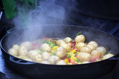 Cooking vegetables in large cast iron cauldron Royalty Free Stock Photos