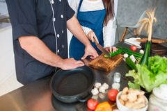 Cooking lessons from the chef for the girl. Close-up of the hand of a girl and a man. Stock Photo
