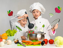Cooking little boy and girl looking in pan Royalty Free Stock Photo