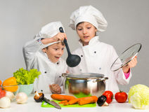 Cooking little boy and girl looking in pan. On table with vegetables Royalty Free Stock Photos