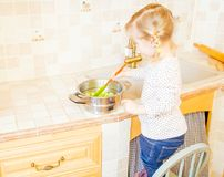 Cooking little lady standing on the chair royalty free stock images