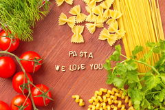 Cooking with love. Different kinds of pasta on wooden background. Stock Photo