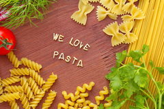Cooking with love. Different kinds of pasta on wooden background. Royalty Free Stock Image