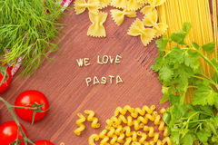 Cooking with love. Different kinds of pasta on wooden background. Stock Photography