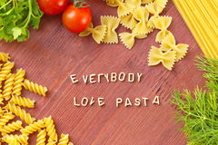 Cooking with love. Different kinds of pasta on wooden background. Royalty Free Stock Images