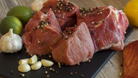 Cooking for lunch the fresh diet of red meat for gourmets. Red meat on a black Board sprinkled with pepper, garlic, anise and lime royalty free stock photo