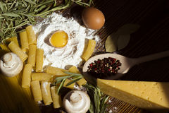 Cooking macaroni ingredients spices egg  rosemary Stock Photography
