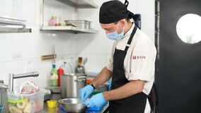 Cooking. man chef, in protective gloves and a mask, prepares food in kitchen, in canteen. health food and safety concept