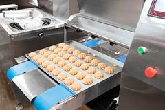 Cooking many sweet meringue on blue production line. sweet food concept.  royalty free stock photography