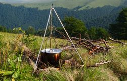 Cooking meal in a kettle on burning campfire in wild camping.  stock image