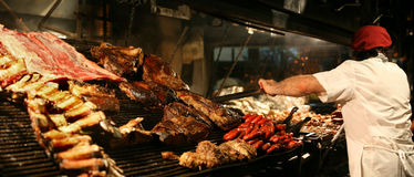 Cooking meat. Argentinian chef cooking meat in the restaurant Royalty Free Stock Photography